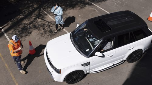 A car departs the new drive-through vaccination clinic at Belmore Sports Ground in Sydney.
