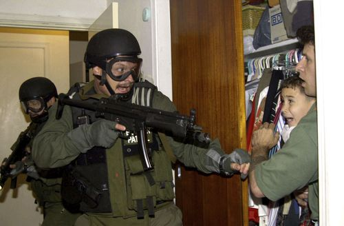 Alan Diaz captured the moment a US immigration agent burst into a Miami home and pointed a gun at six-year-old Cuban boy Elian Gonzalez. Picture: Alan Diaz/AP