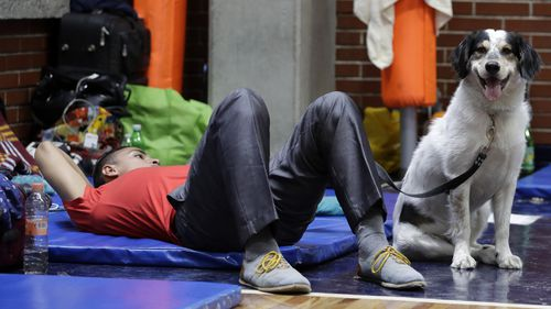 A man rests with his dog Max in a university gymnasium in Del Valle, where around 100 people whose homes were destroyed, damaged or adjacent to damaged buildings have sought shelter. (AAP)