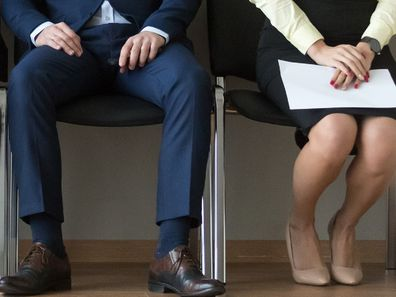 Male job applicants sitting next to woman