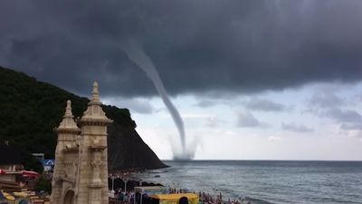 Massive waterspout hovers small distance from seaside resort