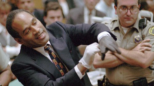 O.J. Simpson grimaces as he tries on one of the leather gloves prosecutors say he wore the night his ex-wife Nicole Brown Simpson and Ron Goldman were murdered, during the Simpson double-murder trial.