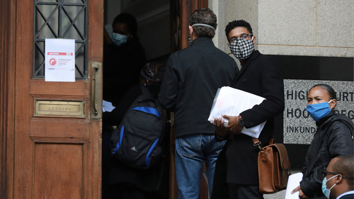 People wearing face masks enter the High Court in Cape Town, South Africa, Tuesday, July 14, 2020, The government has ruled it compulsory to wear face covering in a bid to stem the rising numbers of COVID-19 infections in the country. (AP Photo/Nardus Engelbrecht)