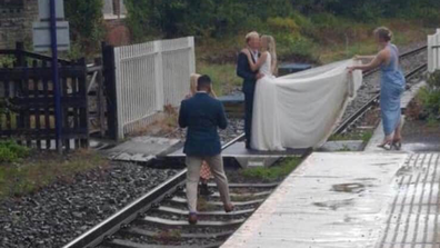Couple take wedding photos on railway
