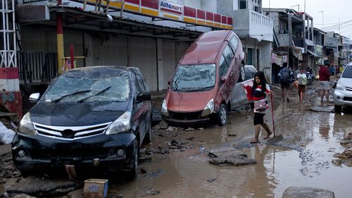 A woman walks past wreckage of cars on a street affected by a flood in Bekasi, West Java, Indonesia, Thursday, Jan. 2, 2020.