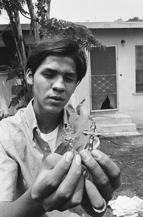Juan Romero, 17, the busboy who tried to aid mortally wounded Senator Robert F. Kennedy, holds crucifixes sent to him to replace the Rosary which he gave to the Senator