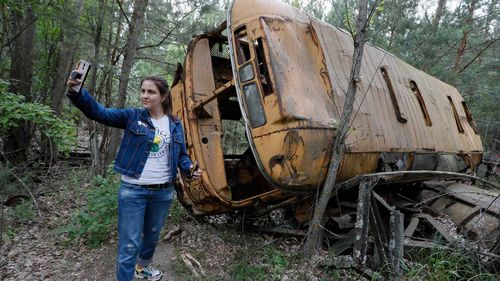 A visitor takes a selfie with an abandoned bus during a tour in Chernobyl.