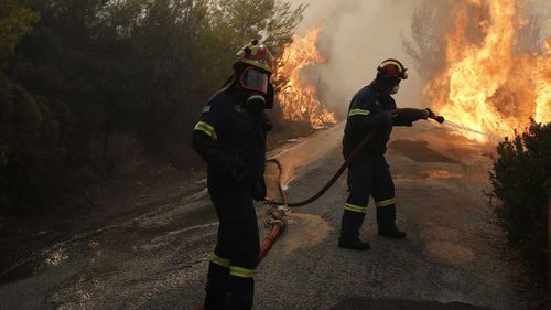 Firefighters try to extinguish a wildfire in Penteli, a northern suburb of Athens, Greece. (AAP)