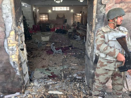 Pakistani security official stands guard outside the destruction caused after a suicide bomb attack at a Christian church, in Quetta, Pakistan. (AAP)