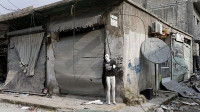 A mannequin placed outside a damaged building .