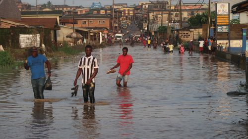 Residents wade through flooded Ige Road, in Aboru, Lagos, after a heavy downpour on July 6, 2020.
