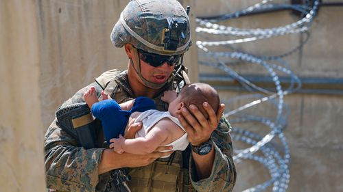 A US Marine assigned to 24th Marine Expeditionary Unit comforts an infant while they wait for the mother during an evacuation at Hamid Karzai International Airport in Kabul.