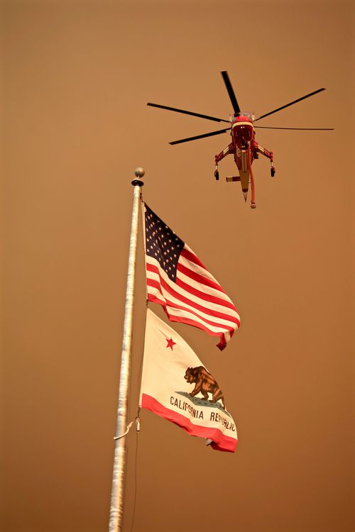 A firefighting helicopter passes over a flagpole with the US and California State flag near the River Fire portion of the Mendocino Complex Fire in Lakeport, California, USA, 29 July 2018 (issued 30 July 2018). The River and Ranch fires combined as the Mendocino Complex Fire with more than 56,000 acres (22,660 hectares) burned, nearly doubling since Sunday with more than 10,000 people already evacuated. EPA/ALAN SIMMONS