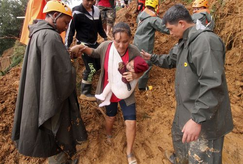 A woman carrying her baby is escorted to safety in Itogon township.