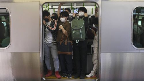 Commuters pack into a train car in Tokyo after a strong earthquake shook the area