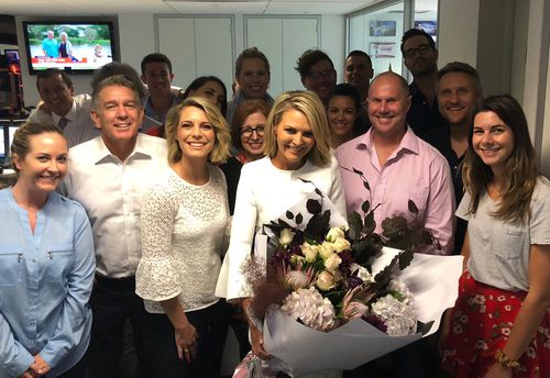 Georgie Gardner this evening with friends and colleagues at Nine News - and a large bunch of flowers.