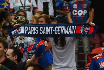 Another fan holds aloft a scarf for Parisian club Paris Saint-Germain.