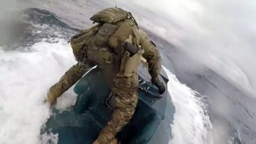 A US Coast Guardsman jumped onto a homemade submarine.