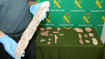 A policeman holds a piece of archaeology recovered by the Spanish Guardia Civil during a joint operation. (AFP)