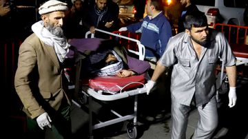 Afghan health workers carry an injured person outside the emergency hospital after a suicide attack targeted a religious gathering at a wedding hall in Kabul, Afghanistan.