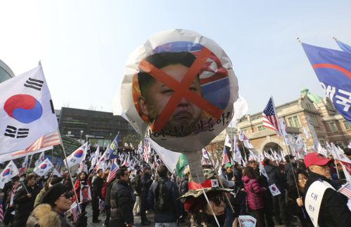 A protester holds a balloon with a defaced portrait of North Korean leader Kim Jong Un during a rally against North Korea's participation yesterday.