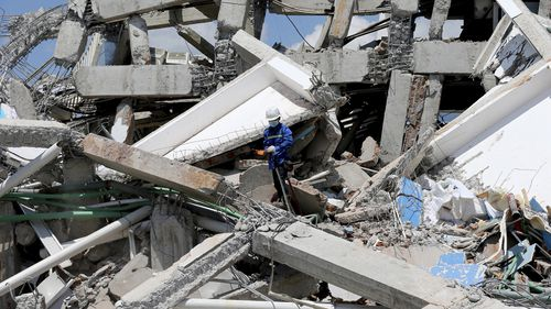 A worker searching the Roa-Roa Hotel for victims.