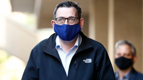 Victorian Premier Daniel Andrews wears a mask as he walks to his daily coronavirus briefing on Sunday.