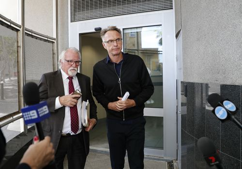 Former Olympic swimmer Neil Brooks walks out with his lawyer Chris Hannay from the Watchhouse after being granted bail yesterday. (AAP)
