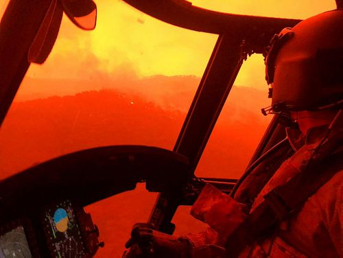 A photograph from inside a helicopter, as it flies above flames and smoke.