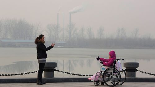 Visitors to a park gestures at each other near chimneys spewing smoke in Beijing. (AP)