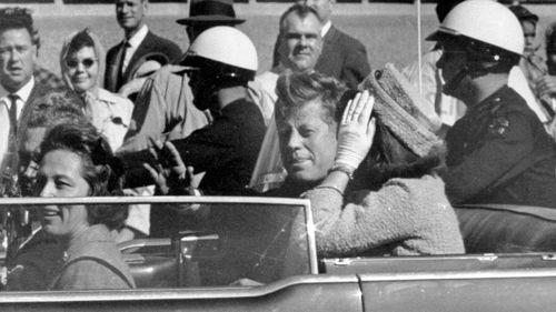John F. Kennedy waves from his car in a motorcade in Dallas (AP Photo/Jim Altgens, File)