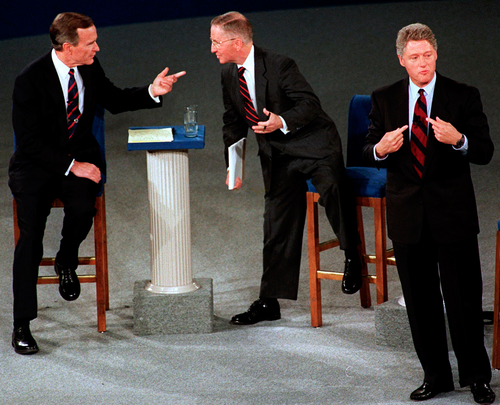 In this 1992 file photo, President George H.W. Bush, left, talks with independent candidate Ross Perot as Democratic candidate Bill Clinton stands aside at the end of their second presidential debate in Richmond.