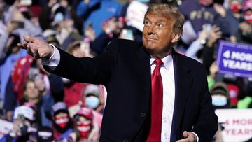 Donald Trump throws his face mask into the crowd before taking to the stage at the Pennsylvania rally.
