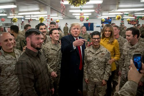 President Donald Trump and first lady Melania Trump pose for a photograph as they visit members of the military at a dining hall at Al Asad Air Base, Iraq.