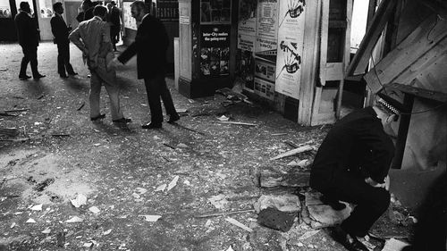 Police inspect the damage in the booking office at Kings Cross station, London, after an IRA bomb exploded in 1973. (AAP)