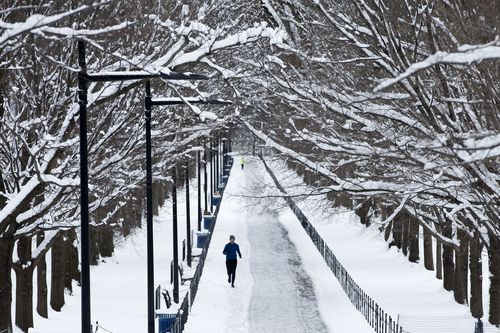 A jogger runs on a snow-covered path near the Lincoln Memorial Reflecting Pool in Washington.