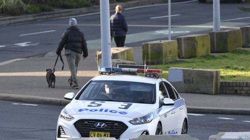 SYDNEY, AUSTRALIA - JULY 11: A police car patrols along Bondi Beach on July 11, 2021 in Sydney, Australia. Lockdown restrictions have been tightened across NSW as COVID-19 cases continue to emerge in the community.  Lockdown restrictions are in place across Greater Sydney, the Blue Mountains, the Central Coast and Wollongong with all residents subject to stay-at-home orders are only permitted to leave their homes for essential reasons, including purchasing essential goods, accessing or providing