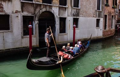 Venice, Italy: Gondola full of tourists on a canal.