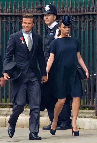 Victoria Beckham, with husband David, in a label of her own design and a Philip Treacy hat at The Royal Wedding in April 2011