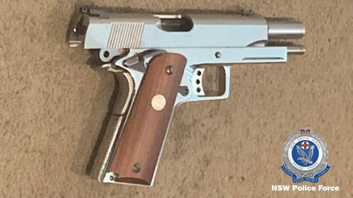 A pistol seized from one of the homes.
