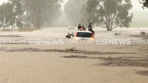 Three other adults and children were trapped on another sinking car. (9NEWS)