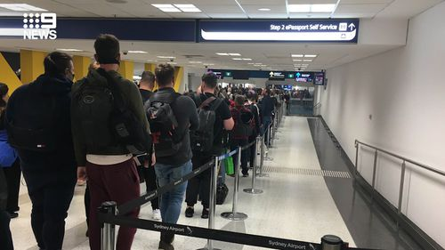 Incoming passengers at Sydney airport wait in line after tough new self-isolation measures were rolled out in Australia.