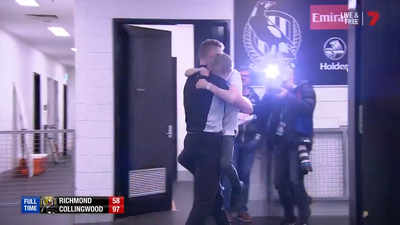 Collingwood coach Nathan Buckley embraces son after momentous AFL finals victory, tumultuous season