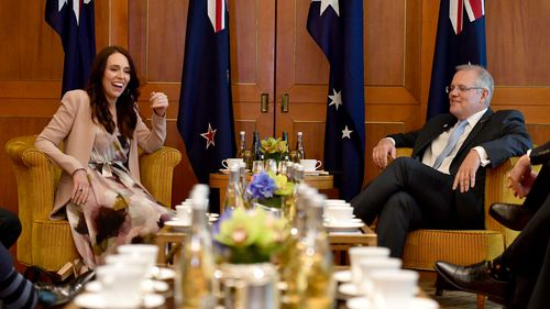 New Zealand Prime Minister and Australian Prime Minister Scott Morrison share a joke during their first face-to-face meeting in Singapore.