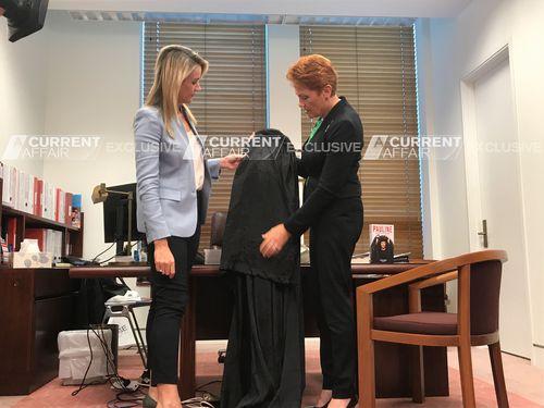 Hanson shows Leila McKinnon her burqa. (A Current Affair)