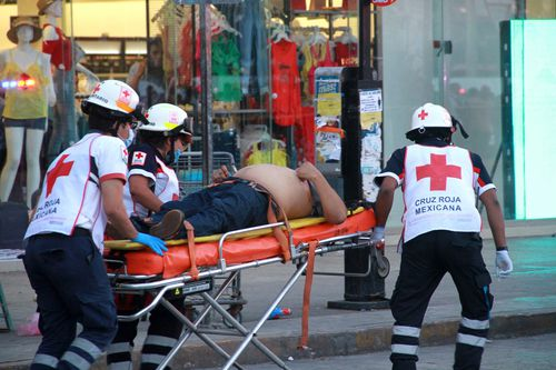 Paramedics rush one of the wounded to hospital in Cancun last Wednesday, following a drive-by shooting at a food stand which left three people dead. (AAP)