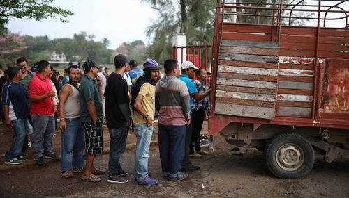 Central American migrants wait in line to receive food. (AP)