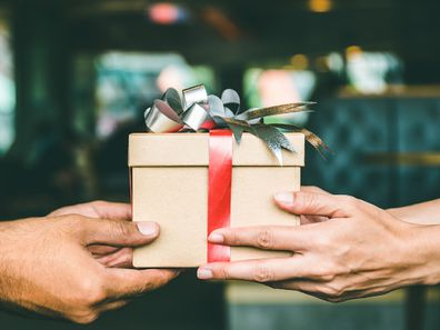 Two people with a Christmas gift in her hands