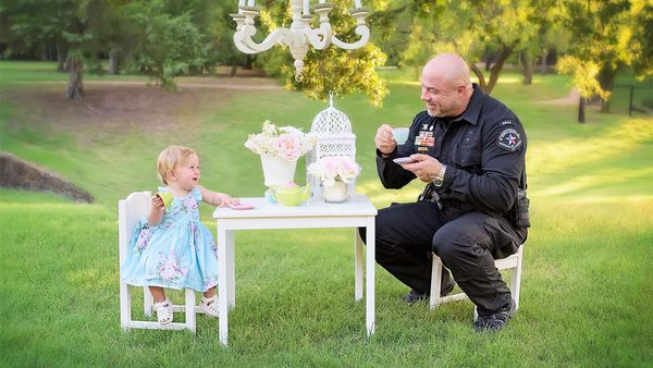 Tea for two: Evelyn Hall celebrates her first birthday with Officer Diebold who delivered her by the roadside. Image: Cyndi Williams Photography