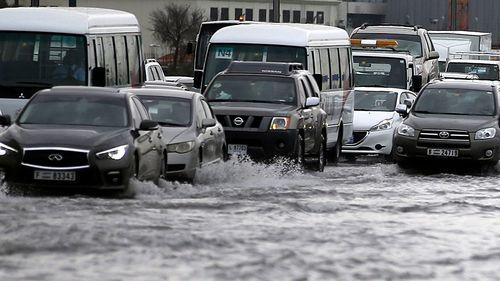 People drive their cars through a flooded street in Dubai. (AAP)